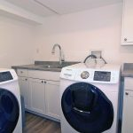 Large laundry room with top of the line washer and dryer, and laundry sink and counter area